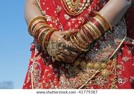 Hands of an Indian bride adorned with jewelery, bangles and painted with henna. - stock photo