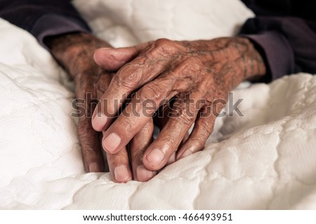 Hands of an old man with wrinkled and wrinkles on a bed
