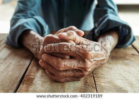 Hands of an old man with wrinkled and wrinkles on the wood table - stock photo