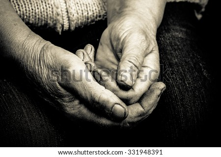 Hands of an old woman lying on her lap. Toned.