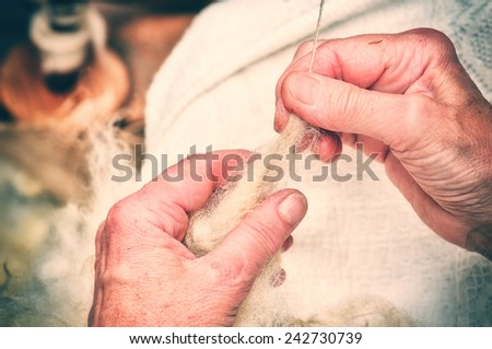 Hands of an old woman making traditional wool spinning - stock photo
