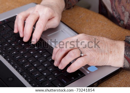 Hands of an old  woman on a computer keyboard - stock photo