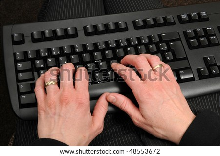 Hands of an older woman on a computer keyboard - stock photo