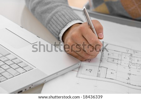 Hands of architect drawing blueprint at desk. - stock photo
