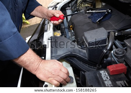 Hands of auto mechanic with wrench. Car repair service. - stock photo