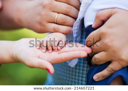 Hands of baby and his mother and father