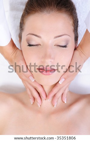 Hands of beautician giving pretty woman face massage - stock photo