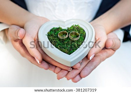 Hands of bride and groom holding a cushion for the rings of wood and green moss in the form of heart.
