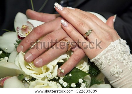 hands of bride and groom near wedding bouquet