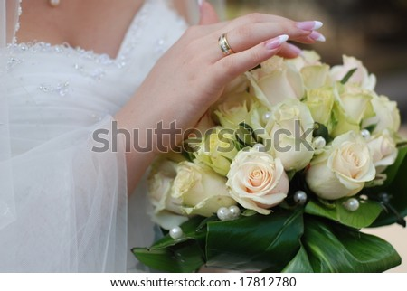 Hands of bride holding wedding bouquet with roses