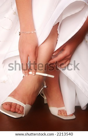Hands of bride putting on wedding shoes. - stock photo