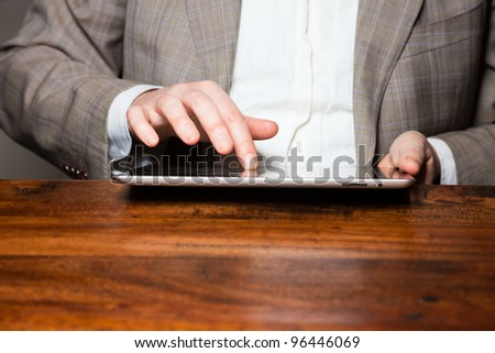 Hands of business man on tablet - stock photo