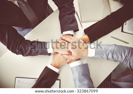Hands of business partners on desk - stock photo