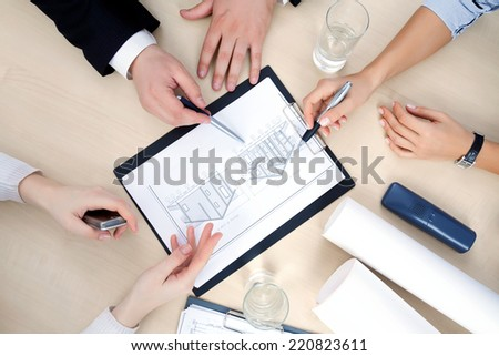 Hands of business people at the table at the meeting in the office. top view - stock photo
