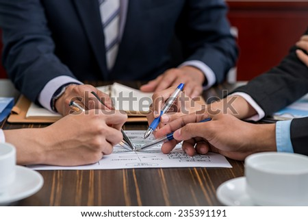 Hands of business people discussing infographics at the meeting - stock photo