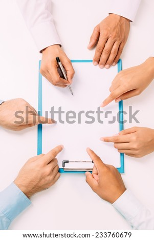 Hands of business people pointing at the document, view from the top - stock photo