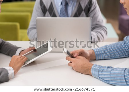 Hands of business people using different gadgets: smartphone, digital tablet and laptop - stock photo