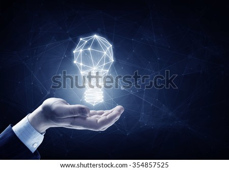 Hands of business person holding illuminated light bulb sign  - stock photo