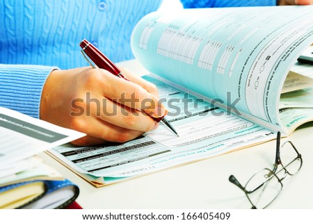 Hands of business woman filling tax form. - stock photo