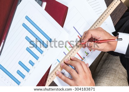 Hands of businessman draw a line on the chart with a ruler and pencil