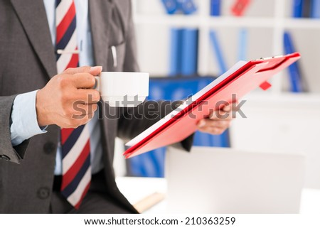 Hands of businessman holding clipboard and coffee cup - stock photo