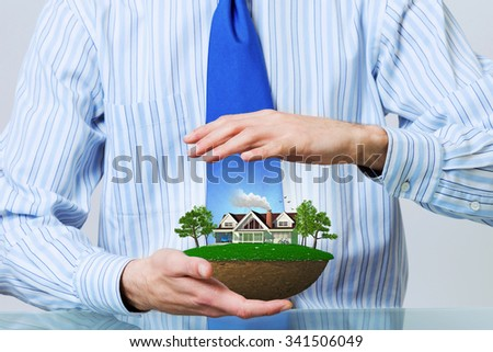 Hands of businessman holding with care green life concept