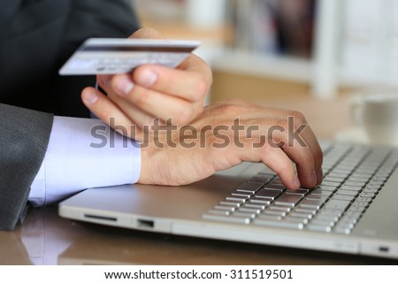 Hands of businessman in suit holding credit card and making online purchase using notebook pc. Shopping, consumerism, delivery or internet banking concept. Anti-fraud and financial security concept - stock photo
