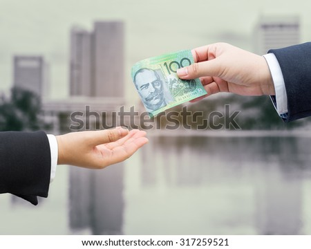Hands of businessman passing Australian dollar (AUD) banknote with blurred office building background. - stock photo