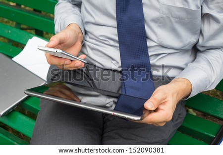 Hands of businessman with mobile phone and tablet. - stock photo