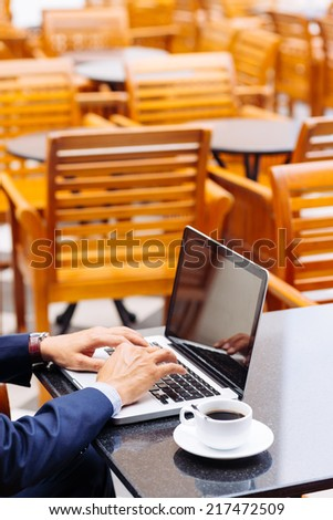 Hands of businessman working on laptop in the cafe - stock photo