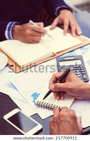 Hands of businessman writing down his timetable - stock photo