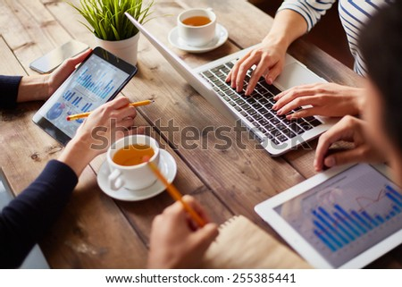 Hands of businesspeople during work with information technologies - stock photo