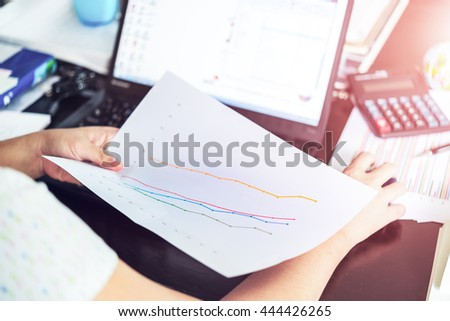 Hands of businesswoman holding analysis chart with laptop and calculator. Accounting. - stock photo