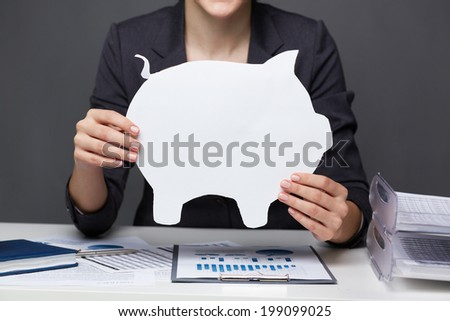 Hands of businesswoman holding paper piggy - stock photo
