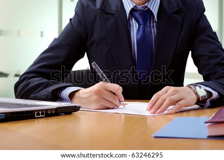 Hands of businesswoman that sitting at the desk in office and signing document