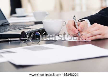 Hands of businesswoman writing something on paper with laptop, cup, pen and documents near by - stock photo