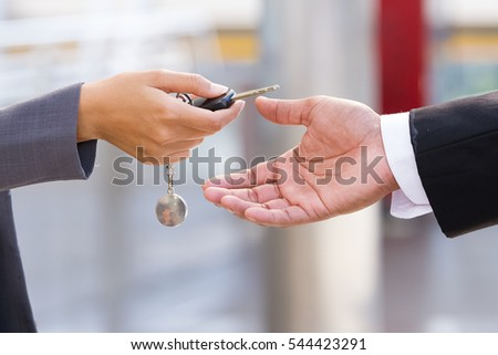 hands of car dealer giving keys to businessman