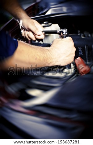 Hands of car mechanic in auto repair service. - stock photo