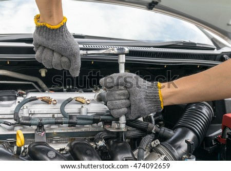 Hands of car mechanic in auto repair service.