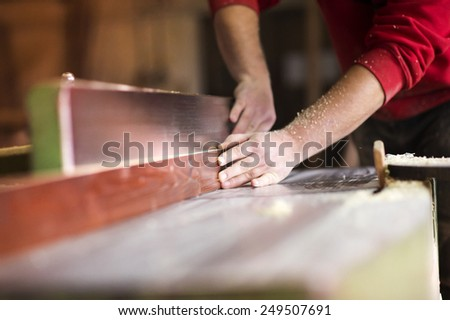Hands of carpenter working with electric wood planer in his workshop - stock photo