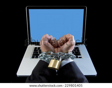 Hands of caucasian businessman addicted to work bond and locked with iron chain handcuffed to computer laptop in workaholic, internet slave and addict concept