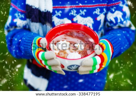 Hands of child holding big cup with snowflakes and hot cocoa and chocolate drink and marshmallows. Kid in winter sweater, long warm scarf and colorful gloves. On cold winter day. - stock photo