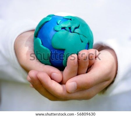 Hands of child holding colorful clay model of Planet Earth with African continent in foreground. - stock photo