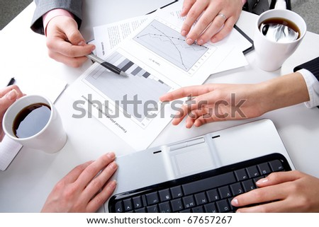 Hands of companions discussing new business strategy at meeting - stock photo