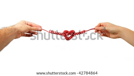Hands of couple holding either end of red telephone line in shape of love heart, isolated on white background.