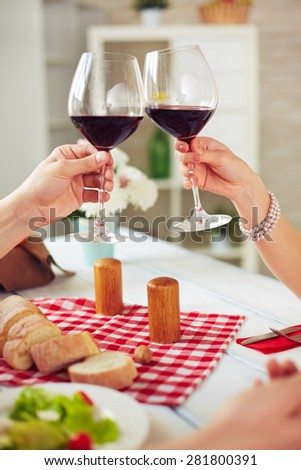 Hands of couple with glasses with red wine during toast - stock photo