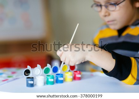 Hands of cute happy preschool kid boy with glasses at home making homework. Little child drawing with colorful watercolors and gouache, indoors. School, education concept - stock photo