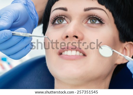 Hands of dentist with dental instruments at the mouth of a young patient. Dentist makes the process of treatment of a beautiful young girl. - stock photo