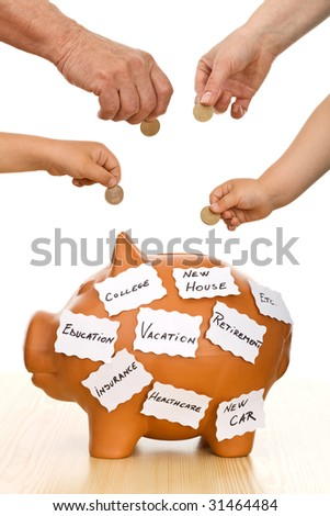 Hands of different generations putting coins into a piggy bank labeled with goals, isolated - home finances - stock photo