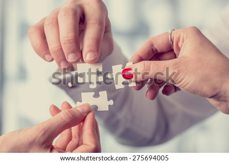 Hands of different people matching together three complementary puzzle pieces, concept of unity and problem solving, close-up with retro filter effect. - stock photo
